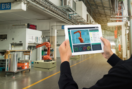 Foto de iot industry 4.0 concept,industrial engineer using software (augmented, virtual reality) in tablet to monitoring machine in real time.Smart factory use Automation robot arm in automotive manufacturing - Imagen libre de derechos