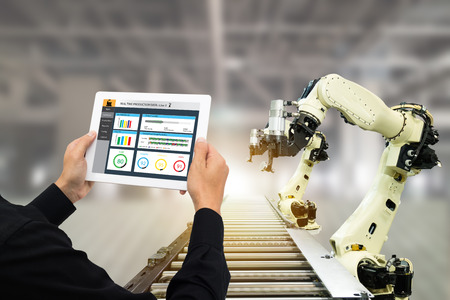 Photo pour iot industry 4.0 concept,industrial engineer using software (augmented, virtual reality) in tablet to monitoring machine in real time.Smart factory use Automation robot arm in automotive manufacturing - image libre de droit