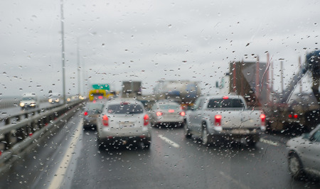 Defocussed traffic viewed through a car windscreen covered in rain, focus on raindrops