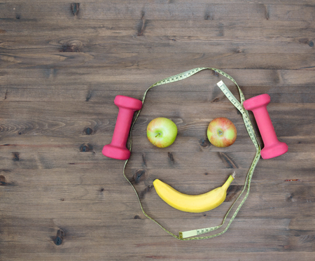 Photo pour Healthy lifestyle concept. colored Apples measuring tape dumbbells banana look like face on  wooden table - image libre de droit