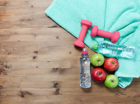 Photo pour Healthy lifestyle concept. colored Apples dumbbells sport water bottles and turquoise towel on wooden table - image libre de droit