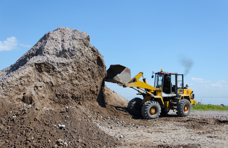 Photo for Wheel excavator digging  gravel pile for loading in the truck - Royalty Free Image
