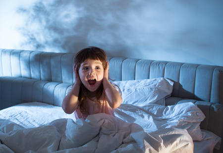 Foto de Night terrors of the child. Fear of the dark. The baby on the bed at night. An empty space to insert text. - Imagen libre de derechos