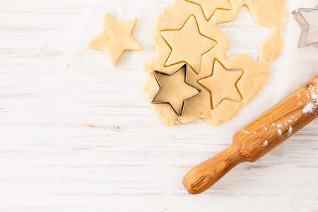 Photo pour The preparation of the biscuits. The dough for making Christmas cookies. The background image of the process of cookie making. - image libre de droit
