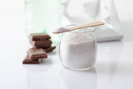 Foto de Stabilizer in the form of powder in a jar with a carbonated drink in a bottle and pieces of chocolate. Stabilizer and sweetener aspartame is used in sweet foods and is harmful to health - Imagen libre de derechos