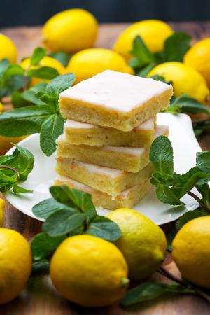 Foto de Sliced shortcake, many lemons and mint on wooden table - Imagen libre de derechos