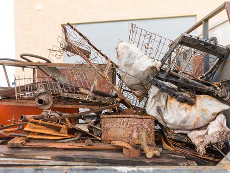 Foto de Fully loaded truck with metal scrap metal parts. Loading scrap in truck. - Imagen libre de derechos