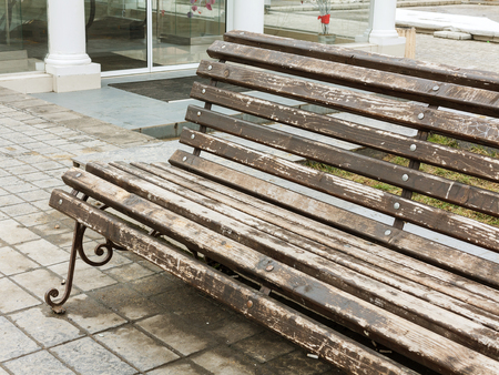 Photo for Fragment of the bench with vintage metal legs close-up, with the remains of cracked peeling brown paint - Royalty Free Image
