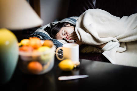 Foto de Sick woman in bed,calling in sick,day off from work.Thermometer to check temperature for fever.Vitamins and hot tea in front.Flu.Woman Caught Cold.Virus.Sick woman laying in bed under wool blanket - Imagen libre de derechos