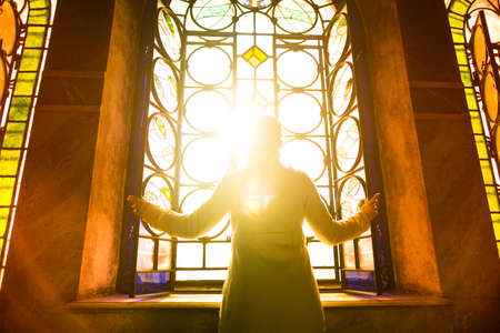 Foto de Religious christian woman looking trough the stained glass church window light.Woman praying to god at St. Alexander Nevsky Cathedral.Finding serenity in religion,faith and hope concept.Enlightenment - Imagen libre de derechos