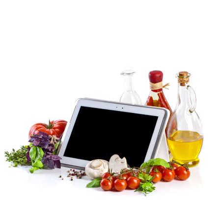 Foto de Tablet computer with vegetables on white background - Imagen libre de derechos