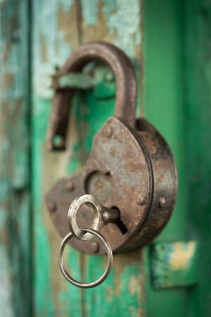 Photo for old padlock with key on a green wooden wall - Royalty Free Image
