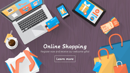 Online shopping concept desktop with computer, table, shopping bags, credit cards, coupons and products