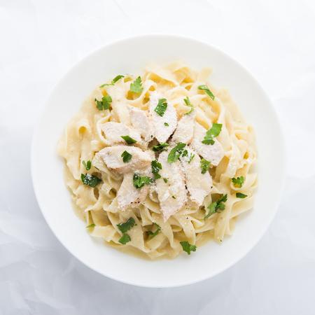 Foto de Pasta fettuccine alfredo with chicken, parmesan and parsley on white background top view. Italian cuisine. - Imagen libre de derechos