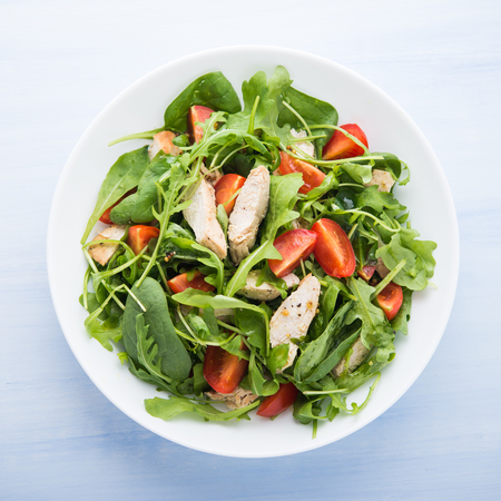 Photo pour Fresh salad with chicken, tomato and greens (spinach, arugula) on blue wooden background top view. Healthy food. - image libre de droit