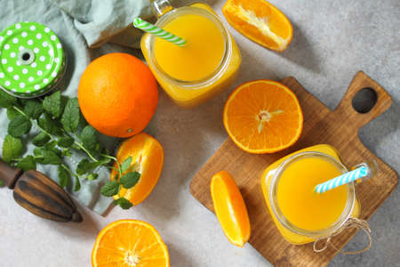 Photo pour Refreshing juice made of orange, cold drink on a stone or slate background. Concept fresh vitamins. Rustic style. Flatlay top view. - image libre de droit