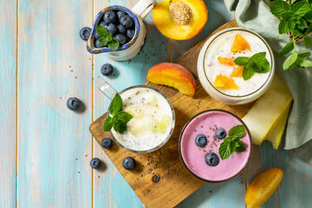 Photo pour Healthy Chia set. Pudding in a glass with blueberry, with melon and peach on wooden kitchen table. Healthy breakfast, vitamin snack, diet and healthy eating. Top view flat lay. Space for text. - image libre de droit