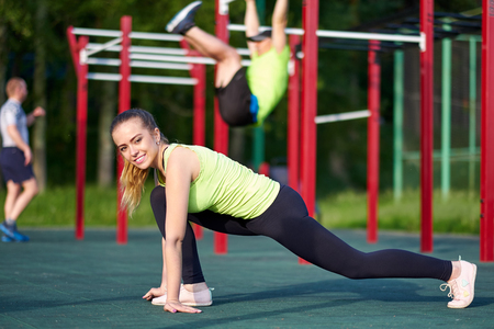 Photo for Happy young woman stretching before running outdoors in workout sports ground. - Royalty Free Image