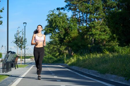 Photo for Young woman running on racetrack during training session. Female runner practicing on athletics race track. - Royalty Free Image