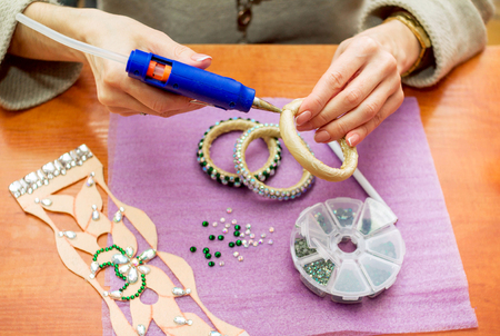 Photo for Close-up woman`s hands, decorating bracelets with colorful shiny rhinestones, gluing crystals on a textile base with hot glue gun. Handicraft process concept. - Royalty Free Image