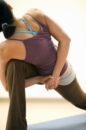 The back of a woman showing her in a bound angle yoga pose. Limited DOF-focus at the hands.