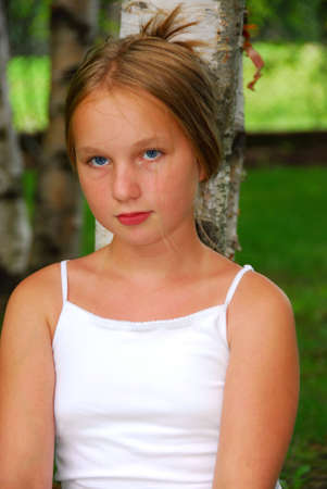 Portrait of a young pretty girl sitting under a birch tree in a park