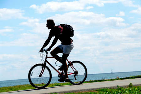 Man riding a bicycle on sea shore trail