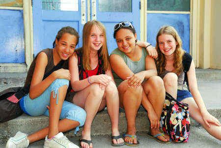 Portrait of a group of young smiling school girls sitting on steps near school building