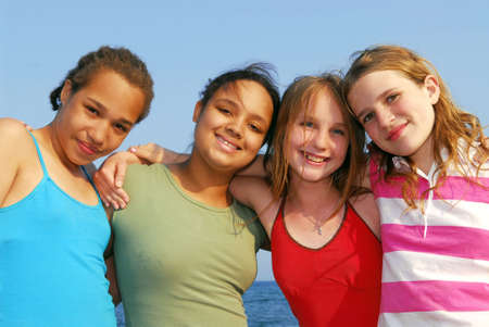 Portrait of four smiling teenage girls outside