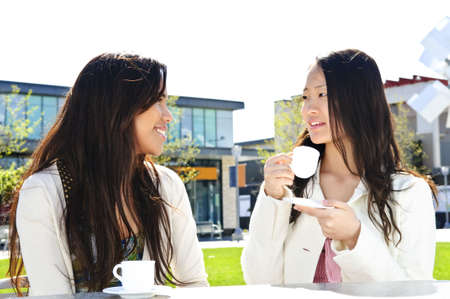 Two girl friends sitting and having drinks at outdoor mall