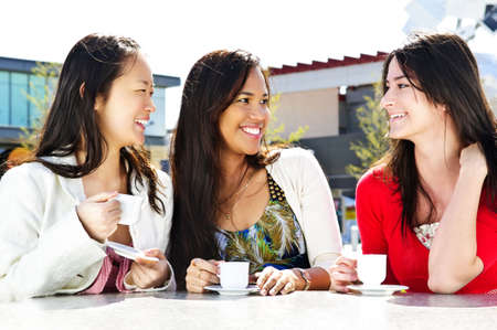 Group of girl friends sitting and having drinks at outdoor cafe