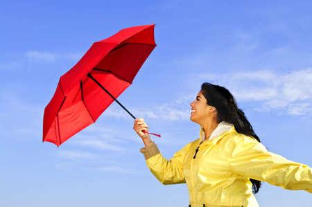 Portrait of beautiful girl wearing yellow raincoat holding red umbrella on windy day
