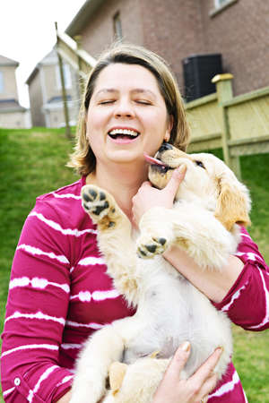 Portrait of laughing woman holding golden retriever puppy
