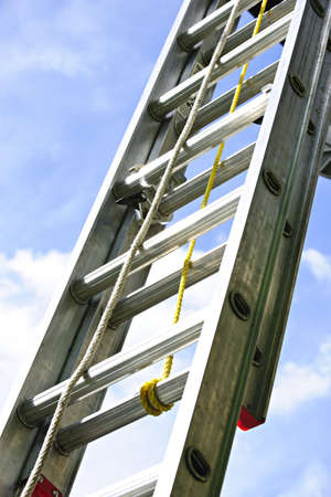 Closeup of construction aluminum extension ladder against blue sky