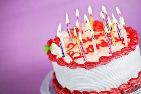 Birthday cake with burning candles on a plate on pink background