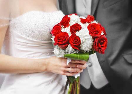 Photo pour Bride and groom holding bridal bouquet close up - image libre de droit