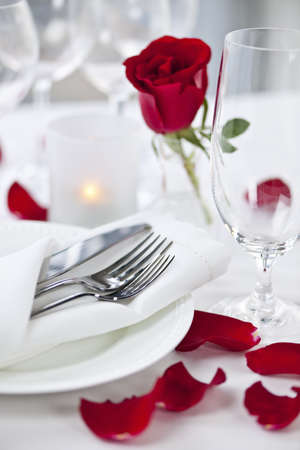 Photo for Romantic table setting with rose petals plates and cutlery - Royalty Free Image
