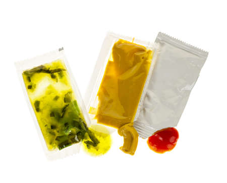 Relish mustard and ketchup condiment packets open on white background