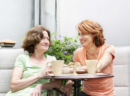 Mature women relaxing and talking with coffee on patio in backyard at home