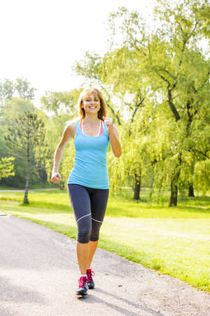 Photo for Smiling woman exercising on running path in green summer park - Royalty Free Image