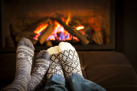 Photo for Feet in wool socks warming by cozy fire - Royalty Free Image