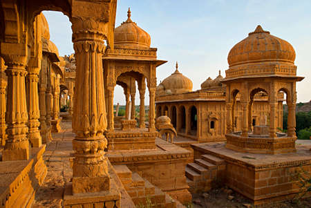 Foto de The royal cenotaphs of historic rulers, also known as Jaisalmer Chhatris, at Bada Bagh in Jaisalmer made of yellow sandstone at sunset - Imagen libre de derechos