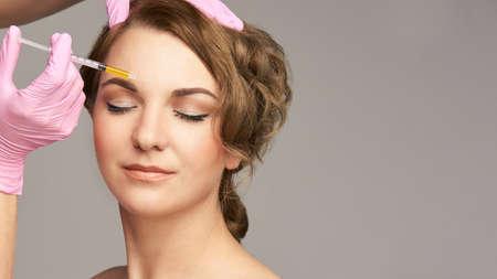 Photo pour Face needle injection. Young woman cosmetology procedure. Doctor gloves. Brow. - image libre de droit