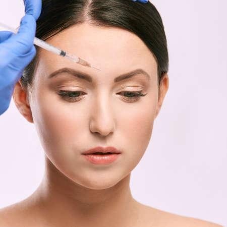 Photo pour Face needle injection. Young woman cosmetology procedure. Doctor gloves. - image libre de droit