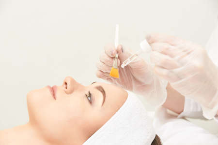 Photo for Young woman cleaning face skin in salon. Retinol peel with brush. Acid organic peeling. - Royalty Free Image