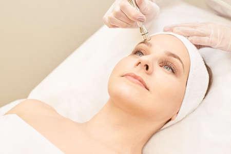 Foto de Cosmetology face treatment. Patient young girl. Salon cosmetic hardware. Dermatology diamond skin clean. - Imagen libre de derechos