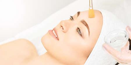 Foto de Facial brush peel retinol treatment. Beauty woman peeling procedure. Cosmetology young girl therapy.Hyaluronic acid. - Imagen libre de derechos