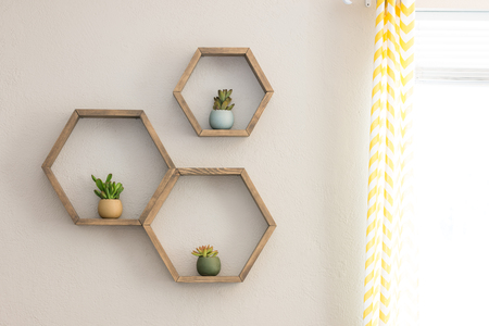 Photo pour Three decorative wooden, floating, hexagon wall shelves, with decorative plants - image libre de droit