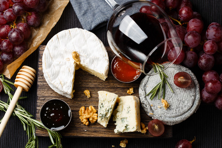 Photo pour Cheese plate served with wine, jam and honey top view - image libre de droit