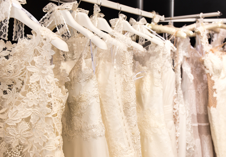 Photo pour white wedding dresses hanging on shoulders and pegs - image libre de droit